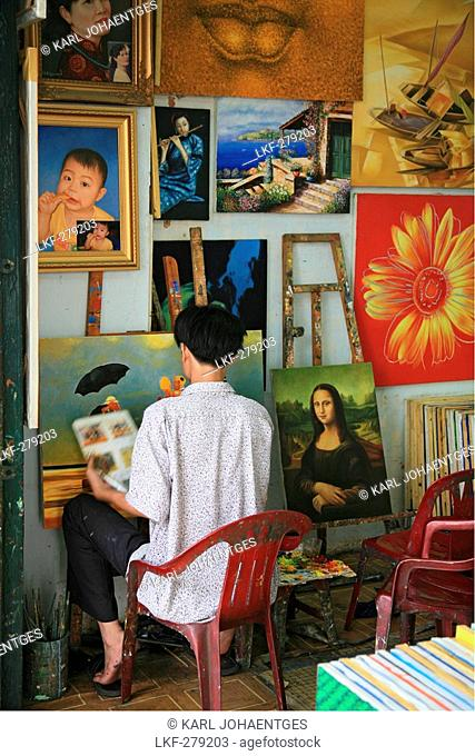 Man and reproductions of famous paintings in a shop, Saigon, Ho Chi Minh City, Vietnam, Asia