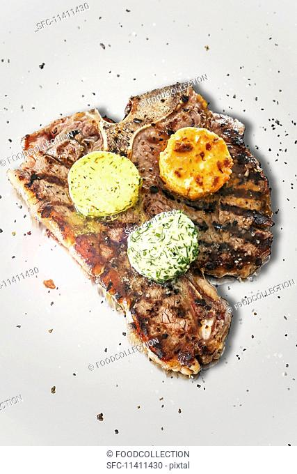 A T-bone steak with three types of herb butter