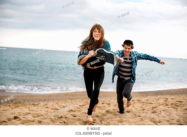 Young couple running and chasing on beach, Barcelona, Spain