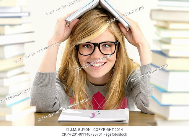 Smiling student teenager holding book over her head sitting desk