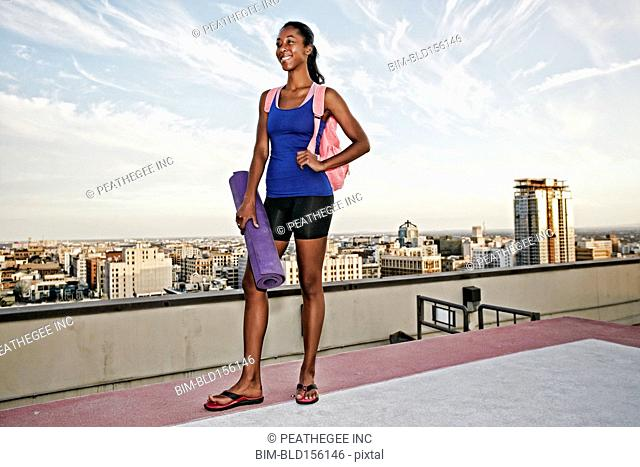 African American woman holding yoga mat on urban rooftop