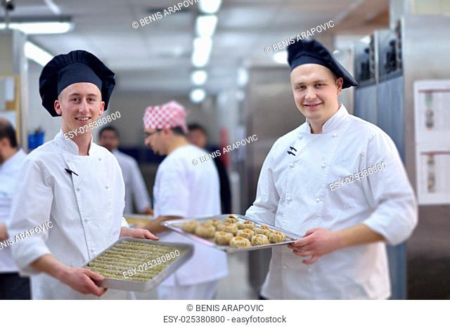 Closeup of a concentrated male pastry chef decorating dessert cake food in the kitchen