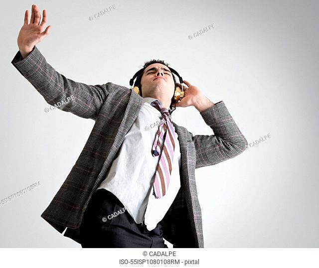 Businessman wearing headphones dancing