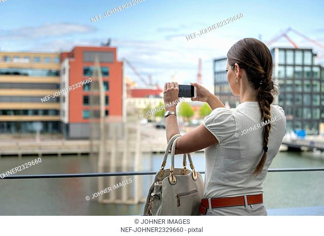 Woman on balcony taking picture