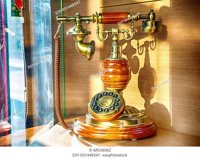 Brown Old-fashioned telephone on the stand, 1900-1920 in the style of old photos, vintage