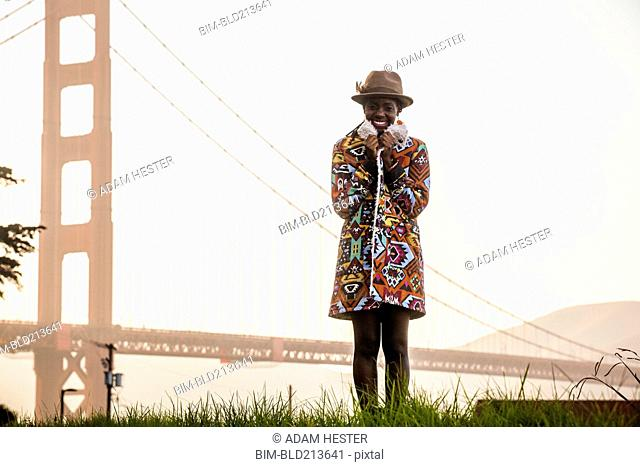 Black woman wearing colorful coat by Golden Gate Bridge, San Francisco, California, United States