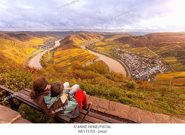 Couple sitting uphill from the famous Moselschleife next to Bremm, where River Moselle makes a 180 degree turn. Lots of rain before the sun peaking through