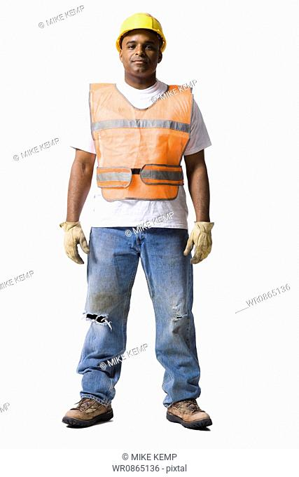 Male road worker with crossed arms and hardhat smiling