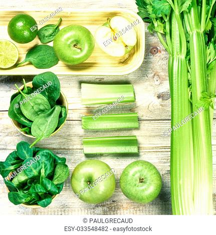 Fresh green vegetables and fruits on wooden background. Detox and diet concept