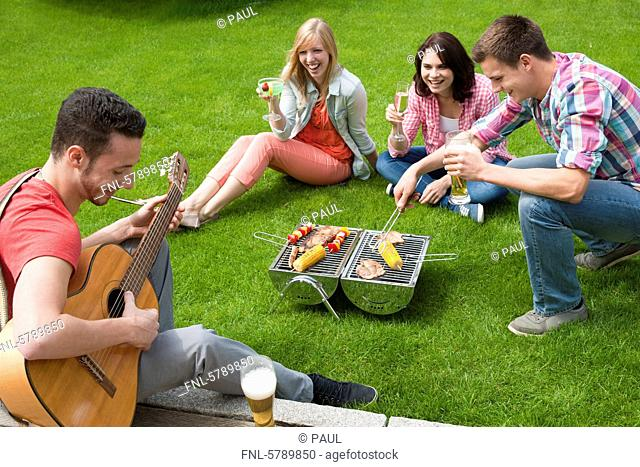 Friends having a barbecue on lawn