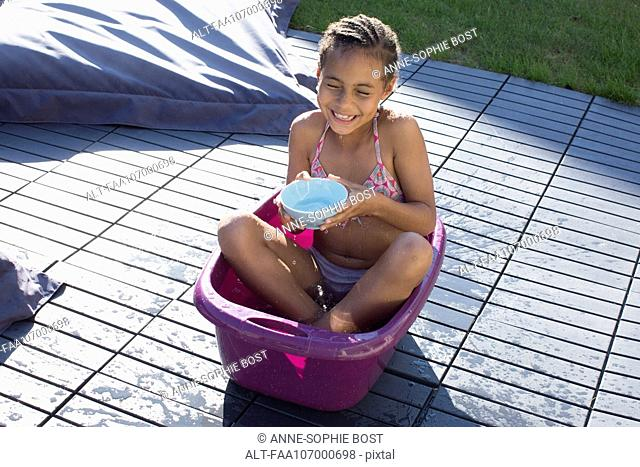 Girl sitting in bucket playing with water