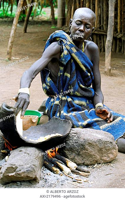 A Mursi tribal woman cooking 'tila' (a traditional dish made with maize or sorghum. Makki /South Omo / Southern Nations, Nationalities & People's Region...