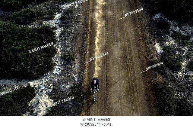 High angle view of man riding cafe racer motorcycle along dusty dirt road