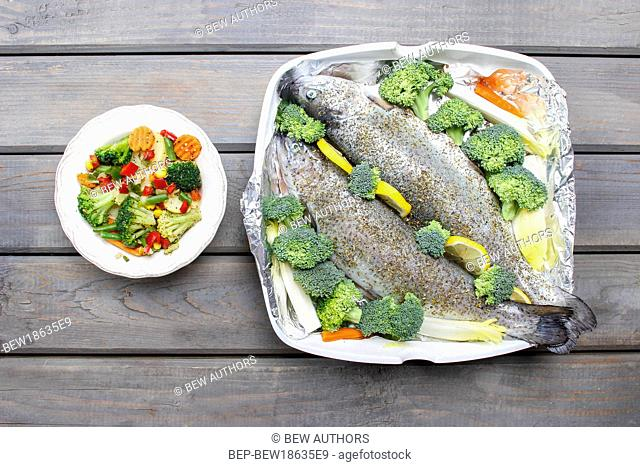 Healthy dinner: trouts and vegetables. Wooden table, top view