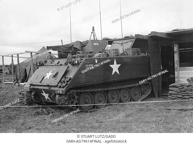 A photograph of an M113 Armored Personnel Carrier, it is backed up to building on base, another building under construction can be seen in the background