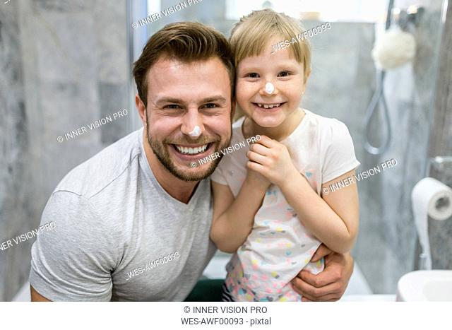 Father and daughter using face cream in bathroom
