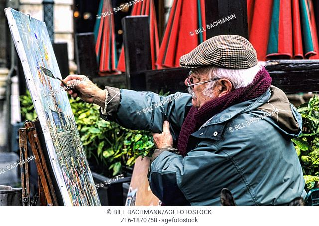 An artist painting painting in the beautiful Grand Place square with 16th Century buildings in Brussels Belgium Europe