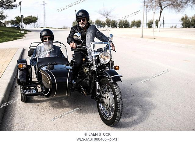 Two bikers standing on a road with their sidecar motorcycle