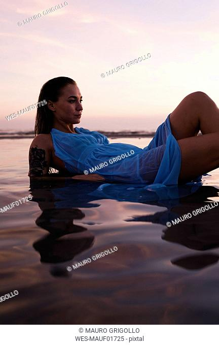 Young woman with tattoo wearing blue dress lying in water at seashore by sunset