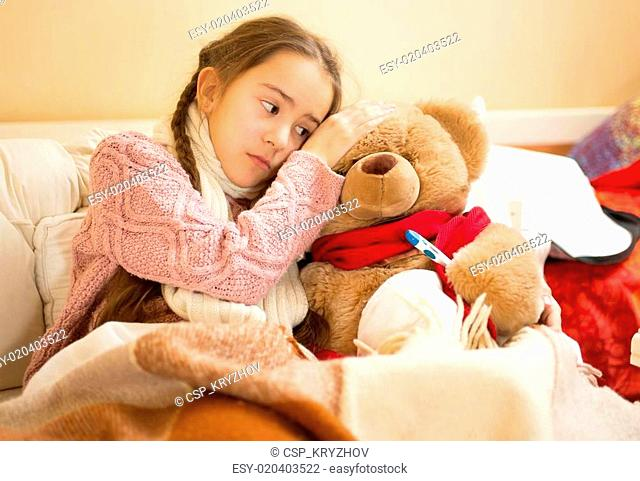 little girl hold hand on teddy bears head and measuring temperat