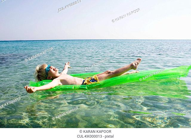 Young boy on an inflatable raft in the water smiling