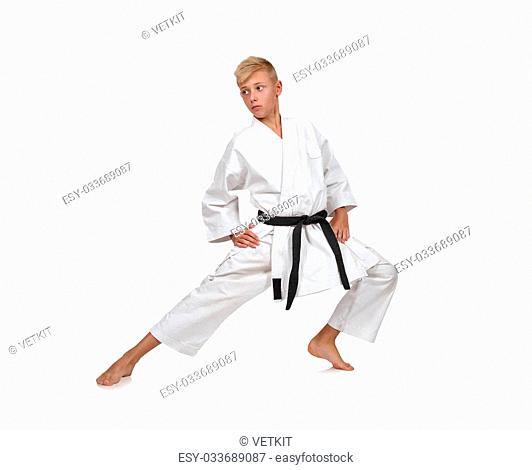 Karate boy in white kimono fighting isolated in white