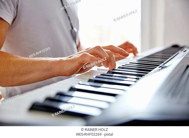 Hands of man playing digital piano