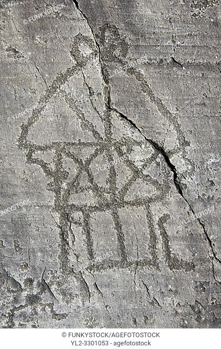 Petroglyph, rock carving, of a house on stilts. Carved by the ancient Camuni people in the iron age between 1000-1200 BC