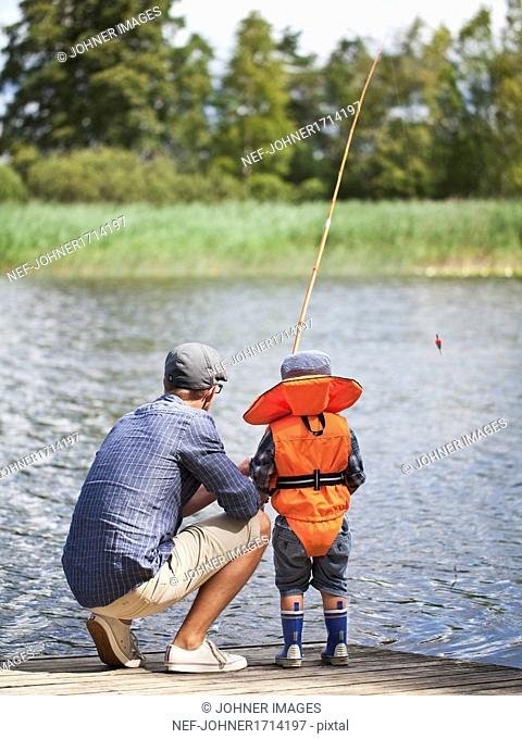 Father with son fishing on jetty