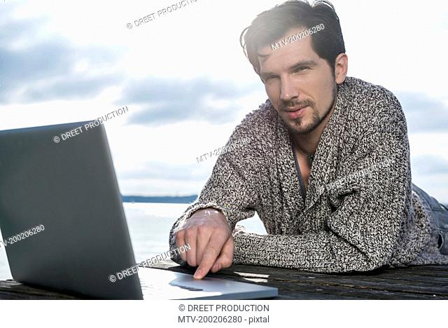 Close up portrait man typing laptop outside