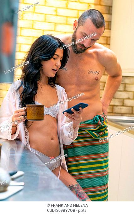 Hipster couple using smartphone in kitchen