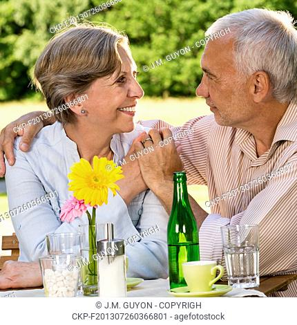 Retired couple sitting at table holding hands outdoors