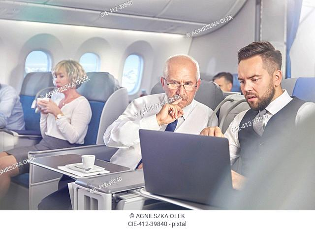 Businessmen working at laptop in first class on airplane