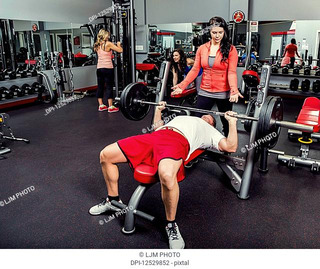 A middle-aged man doing a bench press at a fitness facility while being spotted by his personal trainer; Spruce Grove, Alberta, Canada