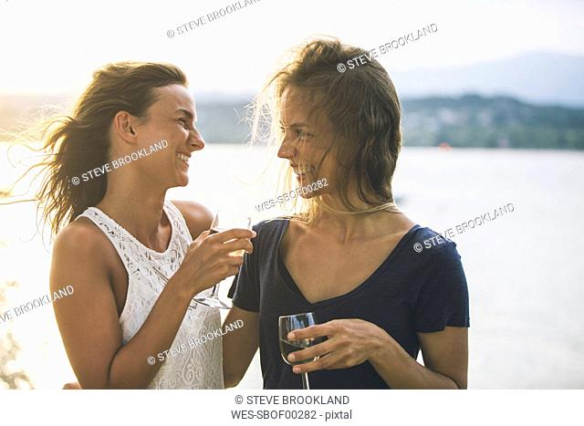 Italy, Lake Garda, two happy young women at lakeshore with glass of wine