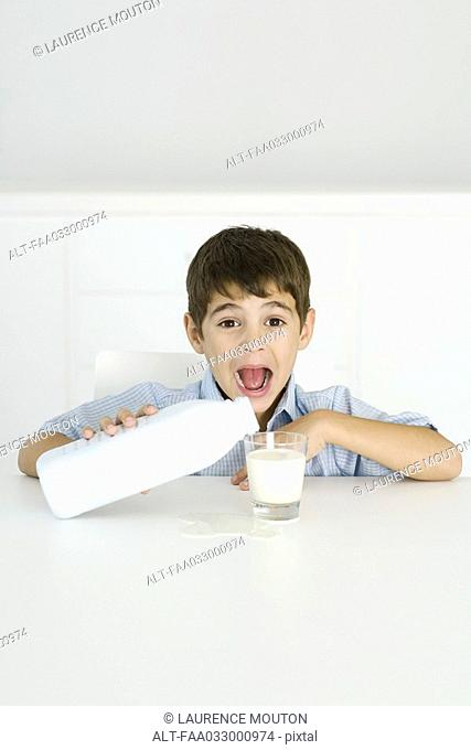 Boy pouring milk into glass, mouth open, spilled milk on table