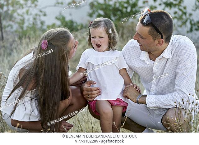 lively daughter toddler between parents, in garden, nature, outdoors