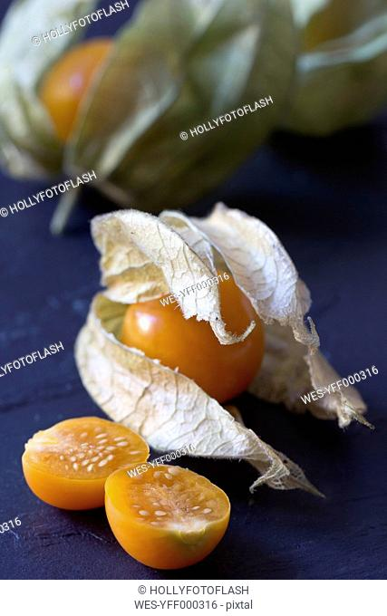 Whole and sliced physalis on slate