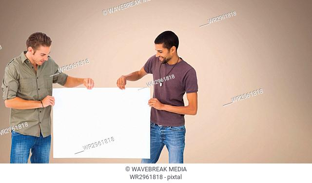 Male friends holding blank billboard against beige background