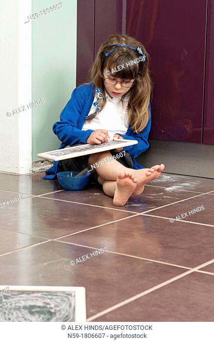Five year old girl in school uniform writing on a small chalk board sitting on her kitchen floor at home