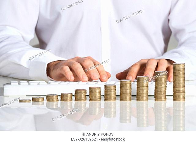 Midsection of businessman using computer keyboard with stacked coins arranged at office desk