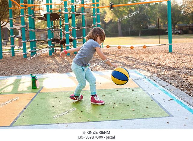 Girl bouncing basketball in playground
