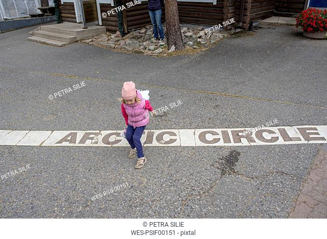 Finland, Rovaniemi, Girl Crossing the Arctic Circle