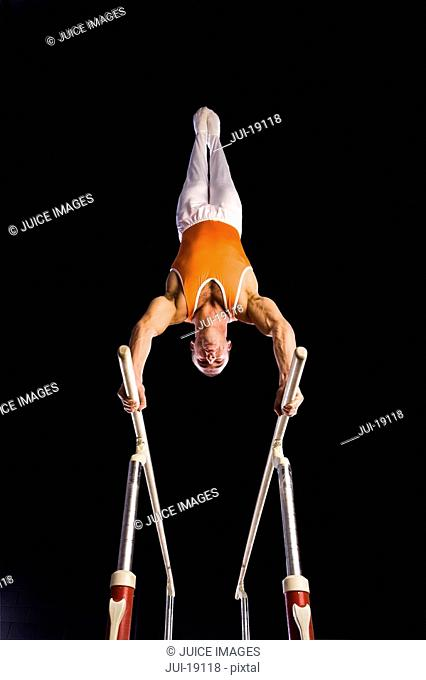 Male gymnast performing on parallel bars, low angle view