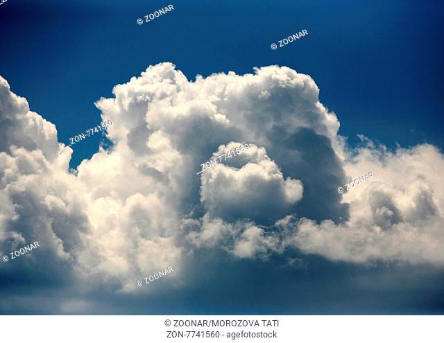 The image of white clouds on a background of the dark blue sky