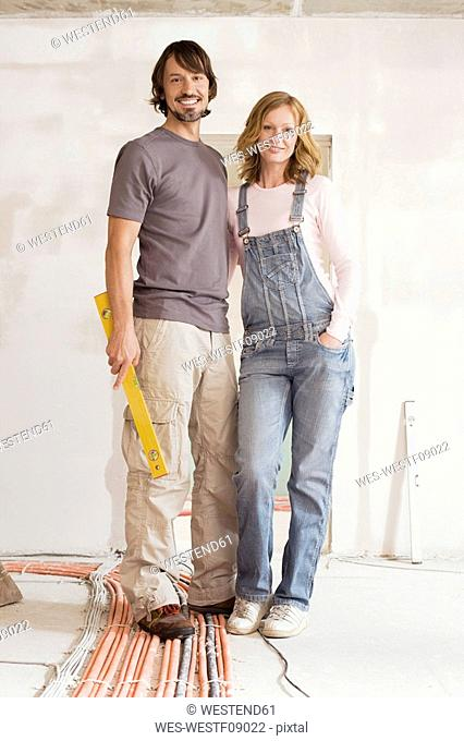 Young couple in an unfinished building, portrait
