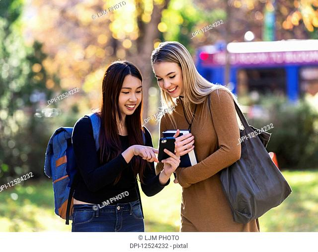 Two university student friends stand together on a university campus looking at a smart phone; Edmonton, Alberta, Canada