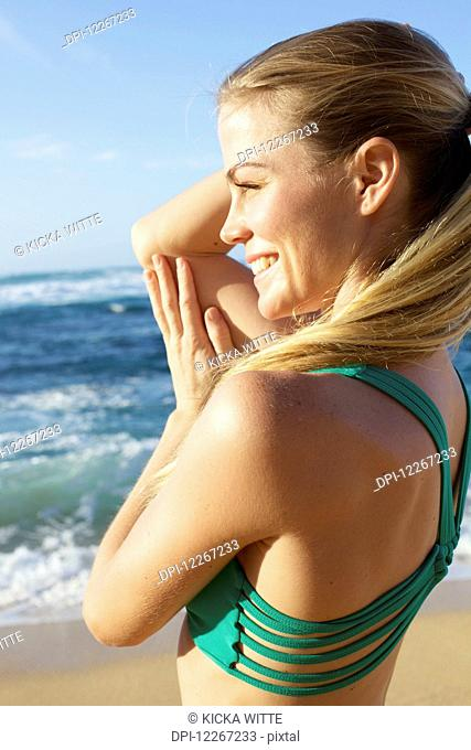 Young woman in fitness attire standing on the beach at water's edge; Kauai, Hawaii, United States of America