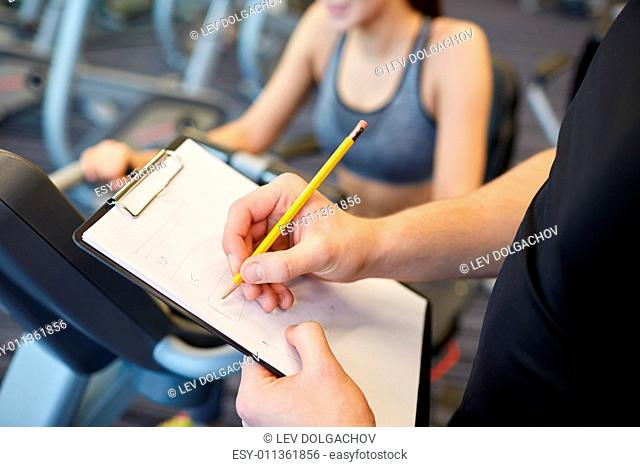 sport, fitness, lifestyle, technology and people concept - close up of trainer hands with clipboard writing and woman working out on exercise bike in gym