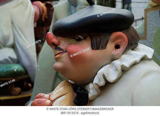 Basque man with a stuck-up nose wearing a beret, crude carnival characters and satirical sculptures at a parade, Fallas festival